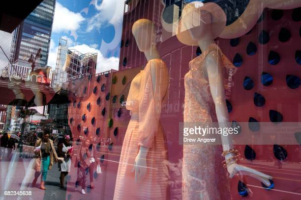 People walk past a store display in the window of Macy's flagship store May 12 2017 in the Herald Square neighborhood in New York City The US...