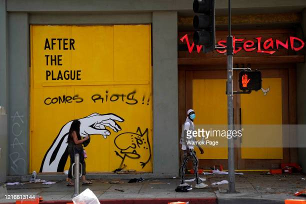 People walk past a store in downtown Santa Monica on May 31, 2020 in Los Angeles, California. Protests continue in cities throughout the country over...
