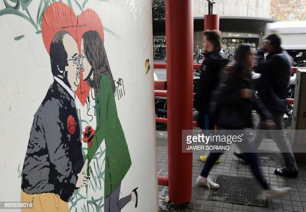 People walk past a street art poster by Italian urban artist Salvatore Benintende aka 'TVBOY' representing Catalan Socialist Party PSC candidate...