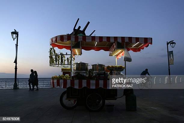 People walk past a street vendor selling corn at sunset on Beirut corniche on April 27 2016 / AFP / PATRICK BAZ