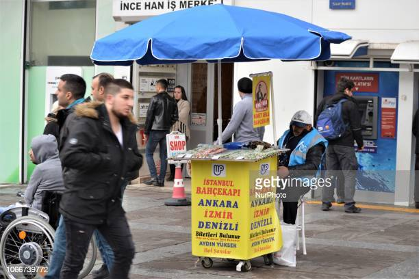 People walk past a street vendor selling New Year's lottery tickets in the Kizilay district of Ankara Turkey on November 30 2018 This year's lottery...