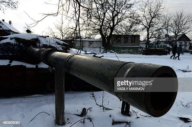 People walk past a tank destroyed by fighting between proRussia and Ukrainian forces in the village of Stepanivka eastern Ukraine on December 30 2014...