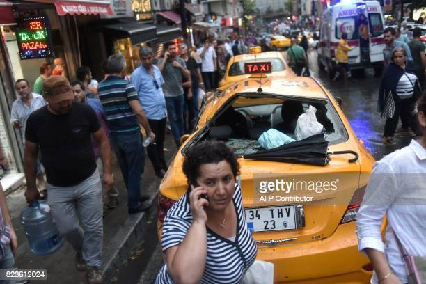 People walk past a taxi with a broken window after the wall of a Christian cemetery collapsed in Istanbul on July 27 during a heavy downpour of rain...