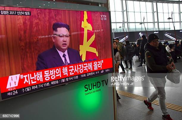 People walk past a television news broadcast at a railway station in Seoul on January 1 2017 showing North Korean leader Kim JongUn's New Year's...