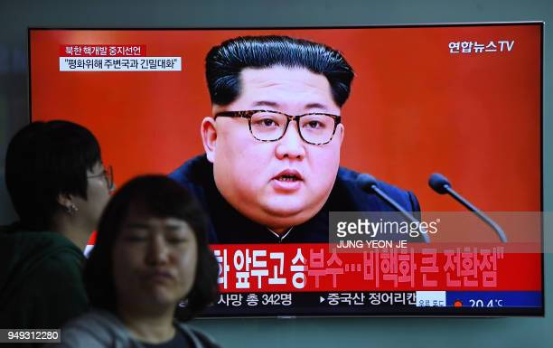 People walk past a television news screen showing a file footage of North Korean leader Kim Jong Un at a railway station in Seoul on April 21 2018...