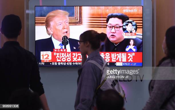 People walk past a television news screen showing North Korean leader Kim Jong Un and US President Donald Trump at a railway station in Seoul on May...