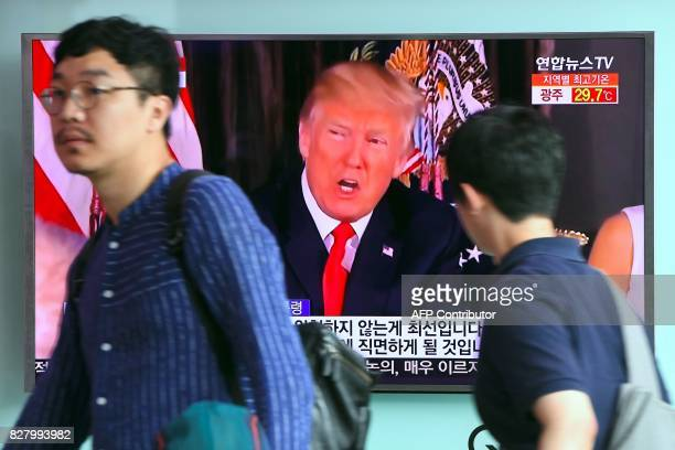 People walk past a television screen showing US President Donald Trump at a railway station in Seoul on August 9 2017 President Donald Trump issued...