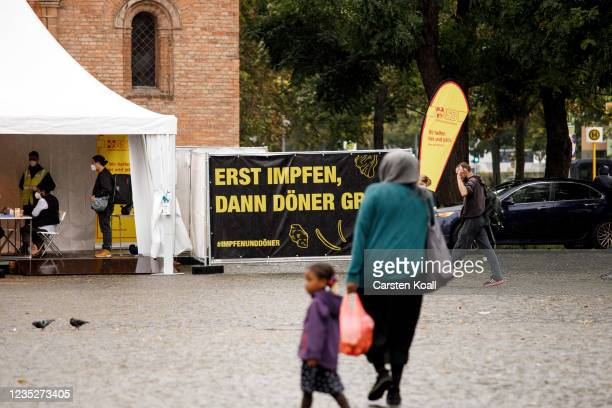 People walk past a temporary vaccination center, where a voucher for a doner kebab is issued after the vaccination, on the third day of the...