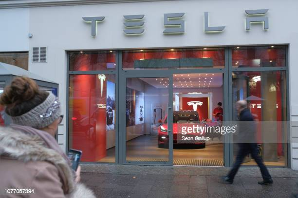 People walk past a Tesla dealership on January 4 2019 in Berlin Germany Tesla is expected to soon begin deliveries of the Model 3 in Europe even...