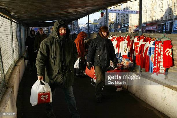 People walk past a trade stand with souvenirs with Soviet symbols on Tverskaya street December 7 2002 in the center of Moscow Russians have started...