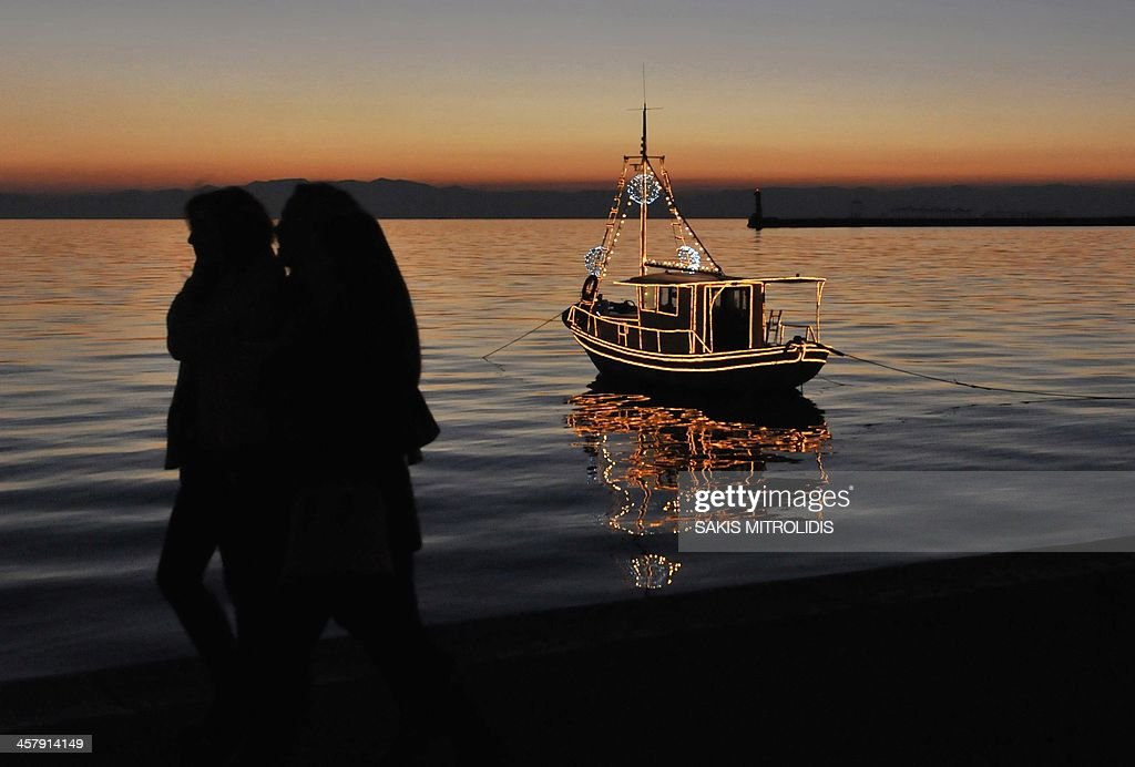 Christmas Boat Greece.People Walk Past A Traditional Christmas Boat Decorated With