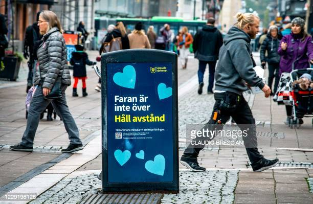 """People walk past a trash can with a sign reading """"The danger is not over - Keep your distance"""" in a pedestrian street in central Uppsala, Sweden, on..."""