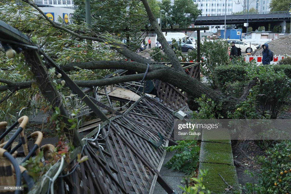 People walk past a tree that was uprooted and smashed a restaurant's outdoor patio during a storm front on October 5, 2017 in Berlin, Germany. Storm front 'Xavier' is hitting northern and central Germany hard, leading to the closure of airports, rail lines, commuter trains and buses and even highways across the region. Authorities are reporting two deaths so far, both in Brandenburg state.