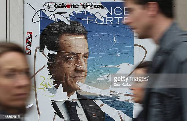 People walk past a vandalised election poster showing French President Nicolas Sarkozy the day before the second rounf of French Presidental...