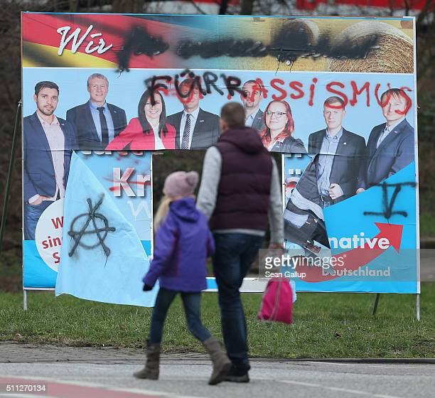 People walk past a vandalized election campaign billboard featuring the populist Alternative fuer Deutschland political party on February 19 2016 in...