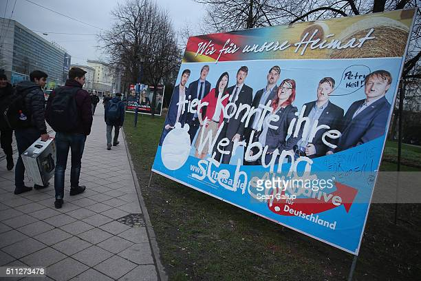 People walk past a vandalized election campaign billboard featuring members of the populist Alternative fuer Deutschland political party painted with...