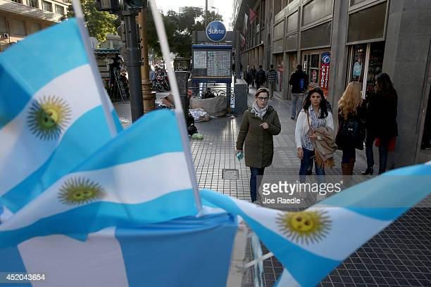 People walk past a vendor selling Argentine flags and other soccer souvenirs as the country prepares for the World Cup final on July 11 2014 in...