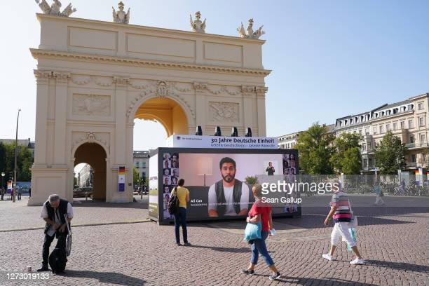 People walk past a video installation showing interviews with a wide range of Germans that is part of an outdoor exhibition marking the upcoming 30th...