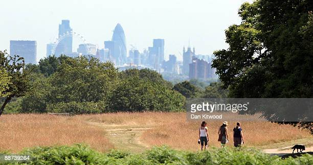People walk past a view of the City of London in Richmond Park on June 29 2009 in London England The Met Office has announced a weather warning for...
