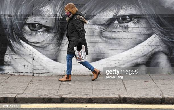 People walk past a wall covered in graffiti art showing a person in a face mask as the general public carry on with their daily chores during the...