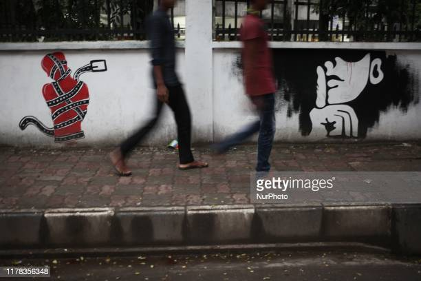 People walk past a wall painting made by students of Bangladesh University of Engineering and Technology in BUET campus in Dhaka Bangladesh on 25...