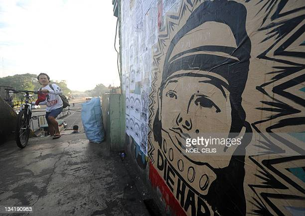 People walk past a wall with a caricature of former Philippine president Gloria Arroyo and Maguindanao massacre suspect Andal Ampatuan at an overpass...