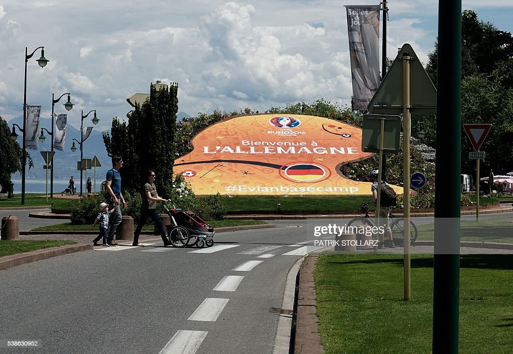 People walk past a welcome sign for the German team in Evian-les-Bains, central-eastern France, on June 7, 2016, three days ahead of the Euro 2016 football tournament. / AFP / PATRIK