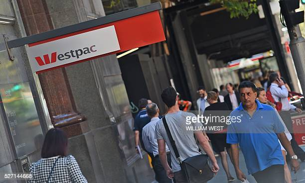People walk past a Westpac Bank sign in Sydney on May 2 as the Australian banking heavyweight posted a three percent rise in interim net profit...