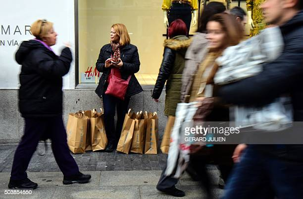 People walk past a woman with shopping bags during the first day of the winter sales in Madrid on January 7 2016 AFP PHOTO / GERARD JULIEN / AFP /...