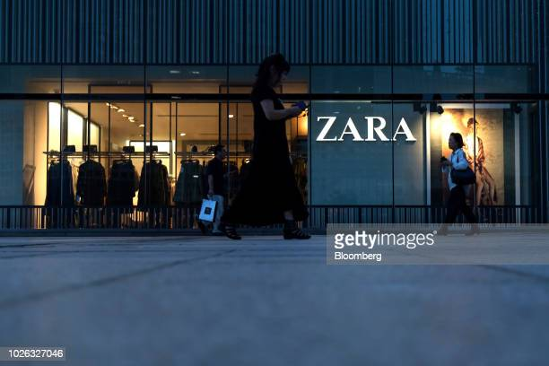 People walk past a Zara fashion store operated by Inditex SA at the Hyundai Development Co I'Park Mall department store at night in Seoul South Korea...