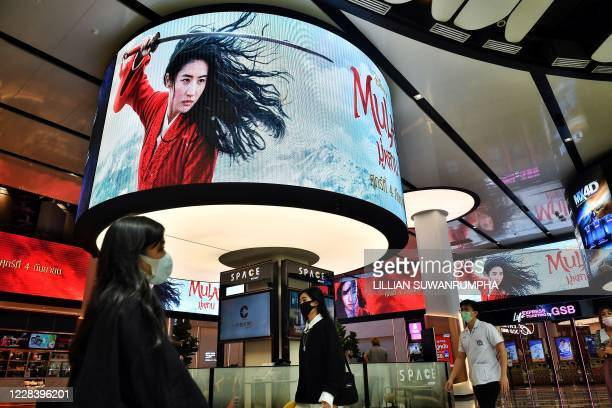 "People walk past advertising displays for Disneys Mulan film at a cinema inside a shopping mall in Bangkok on September 8, 2020. - Disney's ""Mulan""..."