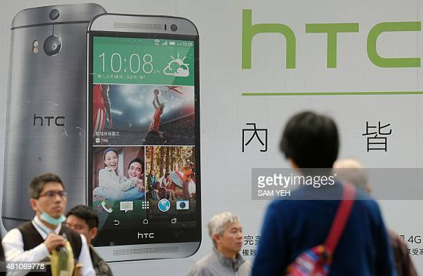 People walk past advertising showing the latest HTC smartphones in Taipei on January 6 2015 Taiwan's smartphone maker HTC said on Janury 6 its net...