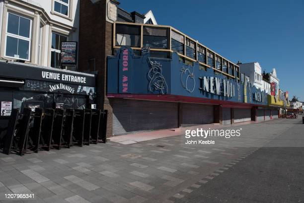 People walk past Amusement arcades closed due to the Coronavirus pandemic on a very quiet seafront on Mother's day March 22 2020 in Southend on Sea...