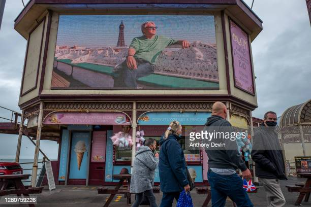 People walk past an advert board on North Pier on October 17, 2020 in Blackpool, England. Lancashire has entered tier 3 of the government's...