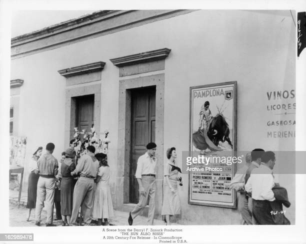 People walk past an advertisement for a bull fight in a scene from the film 'The Sun Also Rises' 1957