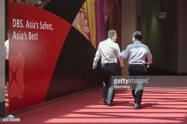 People walk past an advertisement for DBS Group Holdings Ltd outside the bank's flagship branch in Singapore on Thursday Aug 3 2017 DBS Southeast...