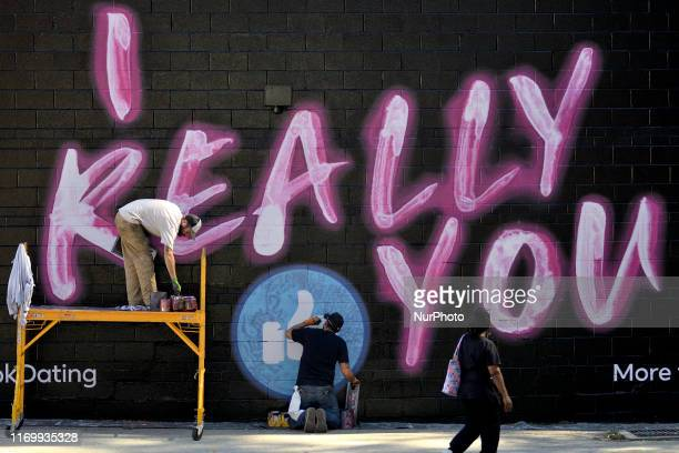 People walk past an advertisement for the Facebook dating service on a sidewall in the Germantown neighborhood of Philadelphia, PA., on September 20,...