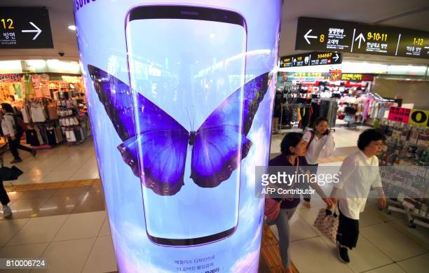 People walk past an advertisement for the Samsung Galaxy S8 at a shoppingmall in Seoul on July 7 2017 Samsung Electronics expects profits to soar 72...