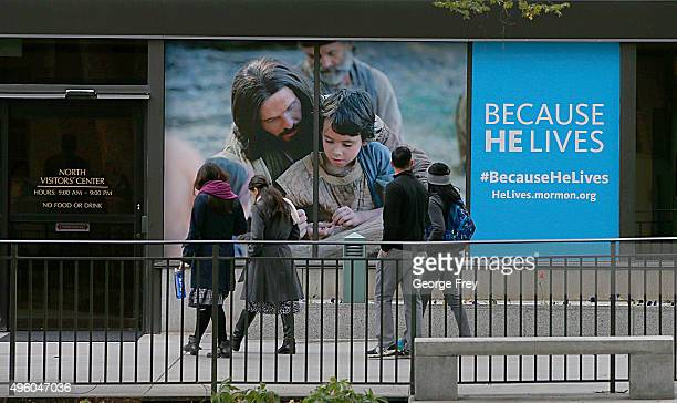 People walk past an advertisement of Jesus with children on the side of the North visitor center of the Mormon Church on Temple Square on November 6...