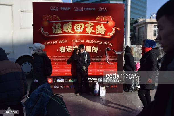 People walk past an advertising board outside a railway station in Beijing on February 10 as travellers depart the capital ahead of the Lunar New...