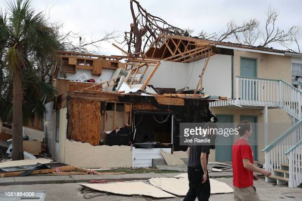 People walk past an apartment destroyed by Hurricane Michael on October 11 2018 in Panama City Florida The hurricane hit the Florida Panhandle as a...