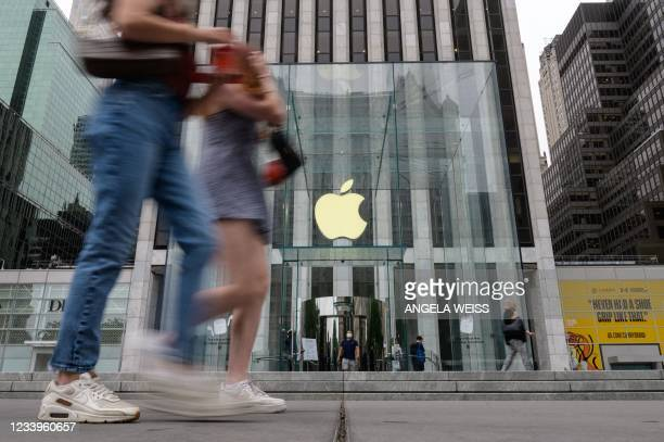 People walk past an Apple retail store on July 13, 2021 in New York City. - Stock markets were slightly softer on news of the biggest jump in US...