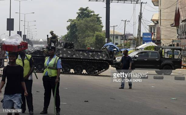People walk past an Armoured Tank mounted by soldiers on the main road leading to the Independent National Electoral Commission headquarters in Port...
