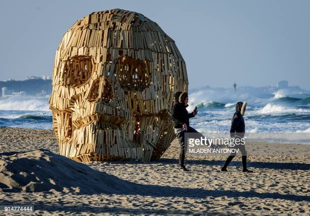 TOPSHOT People walk past an artist creation at Gyeongpo beach in Gangneung ahead of the Pyeongchang 2018 Winter Olympic Games on February 6 2018 /...