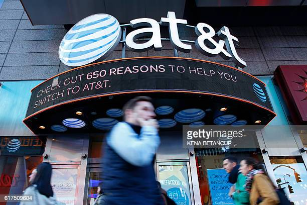 People walk past an AT&T store in New York on October 23, 2016. AT&T unveiled a mega-deal for Time Warner that would transform the telecom giant into...