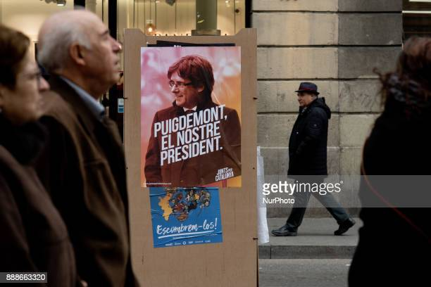 People walk past an election campaign poster of the candidate of the Junts Per Catalunya party and Catalonia's deposed regional president Carles...