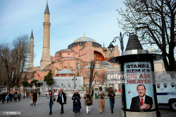 People walk past an election poster bearing the picture of Turkish President Recep Tayyip Erdogan and reading Istanbul is a love story for us in...