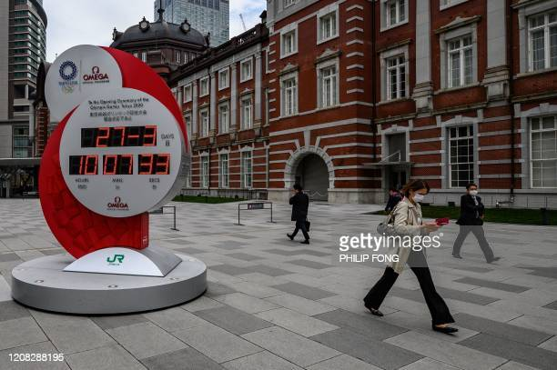 People walk past an electronic 2020 Tokyo Olympic Games countdown clock showing today's date and local time instead of the countdown days outside...
