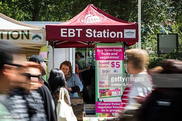 People walk past an Electronic Benefits Transfer station more commonly known as Food Stamps in the GrowNYC Greenmarket in Union Square on September...