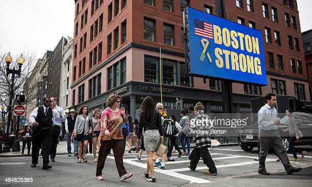 People walk past an electronic billboard reading 'Boston Strong' near the finish line of the Boston Marathon on April 14 2014 in Boston Massachusetts...